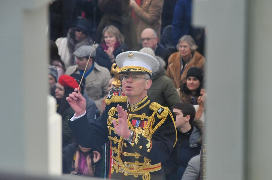 Vermont's Colonel Michael Colburn conducting the Marine Band, as seen through an opening in the Inaugural Platform.